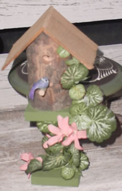 Minature log bird house on pedistal